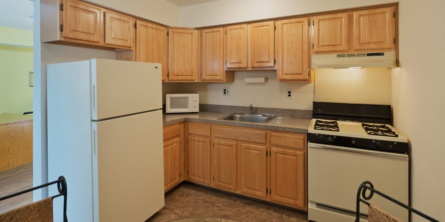 Kitchen in Maple Shade Apartment for rent with wooden cabinets and white appliances.